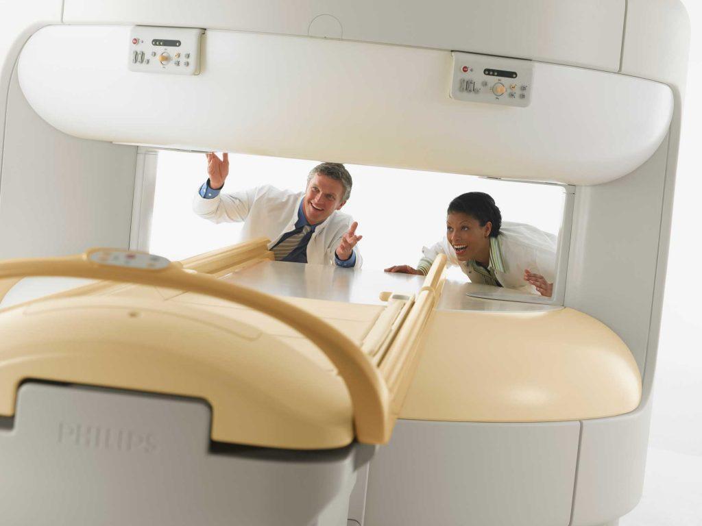 Arzt und MTRA stehen hinter dem offenen MRT